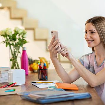 En kvinne sitter ved et bord og bruker sin smarttelefon for å skriver ut merkelapper og silkebånd via Bluetooth