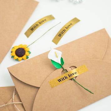 En brun konvolutt som er pyntet med en blomst som er festet med en merkelapp med sort tekst på glitrende gull