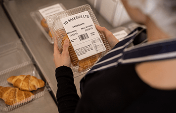 Woman wearing blue and white striped apron holding plastic bakery product with label