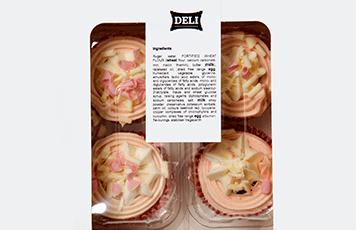 Rosa og hvit cupcakes i en hvit og klar plastboks, med en ingrediens etikett