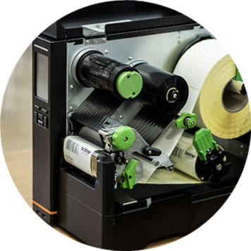 Machine open, white roll of labels, green mechanisms, rollers
