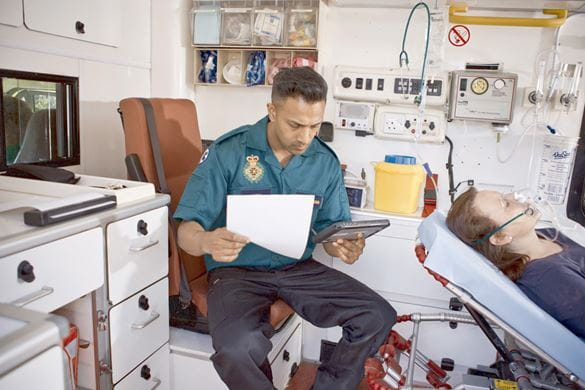 Ambulansepersonellsom sitter i en ambulanse med et nettbrett og en mobil skriver i Brother PJ700-serien
