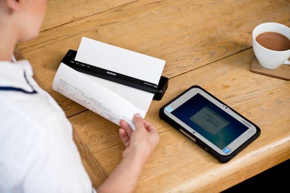En helsearbeider skriver ut en pleieplan på en mobil skriver i PJ-serien fra Brother