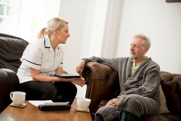 Kotihoidon miespotilas ja sairaanhoitaja keskustelevat