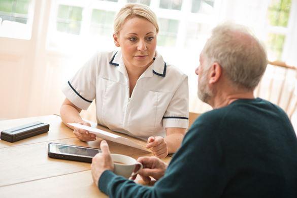 Omsorgsarbeider som snakker med en pasienten hjemme