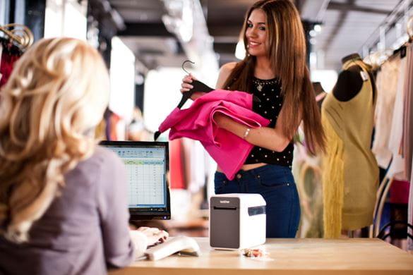 Nainen ostaa pinkkiä takkia myymälässä ja kuitti tulostuu TD-2000-tarratulostimesta