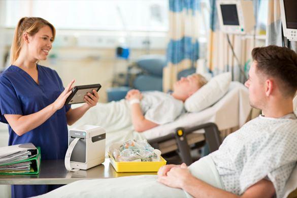 En sykepleier i samtale med en pasient som ligger i en sykehusseng