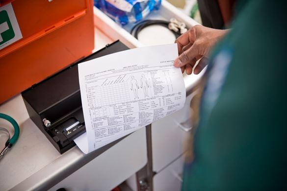 En ambulansearbeider skriver ut et  A4-dokument i ambulansen på en mobil skriver fra Brother
