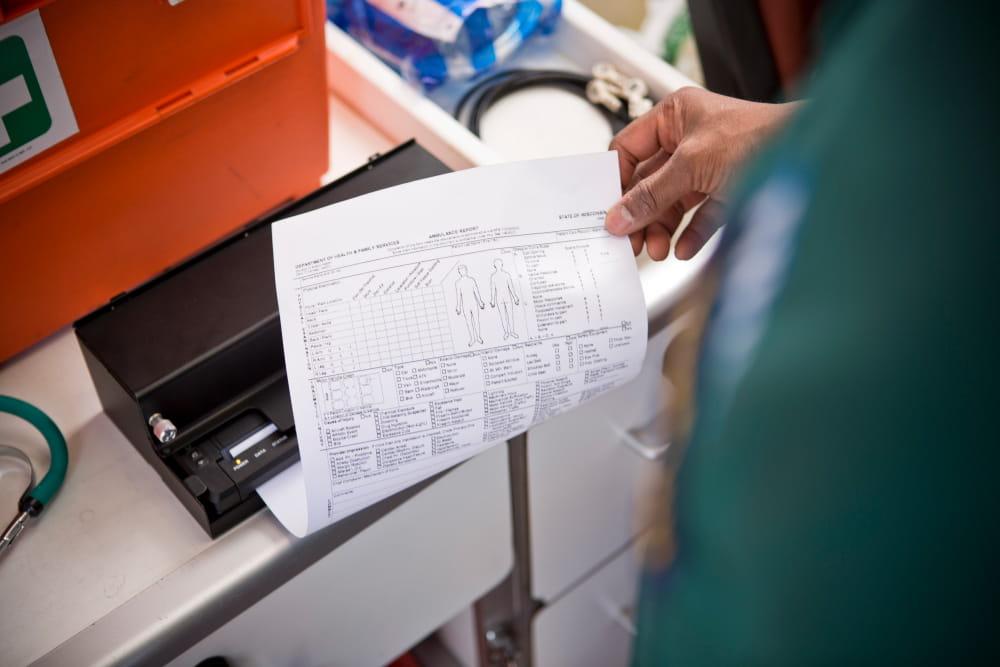 Mies tulostaa A4-asiakirjaa ambulanssissa