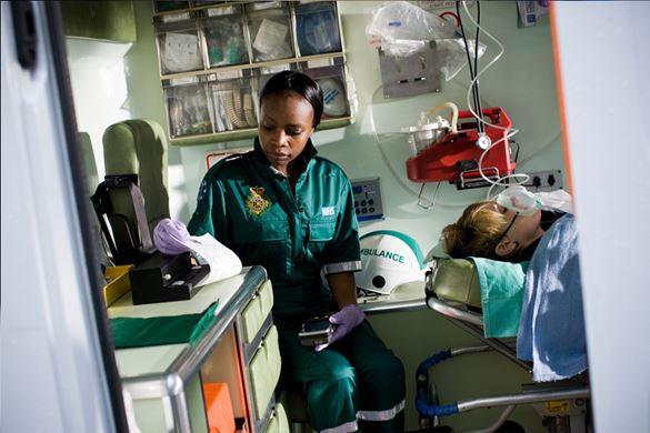 En abulansearbeider som sitter i en ambulanse og skriver ut et dikument på en mobil skriver fra Brother