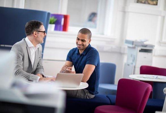 Två män diskuterar vid ett bord