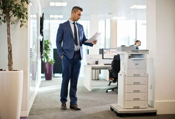 Mann på et kontor ved gulvplassert skriver