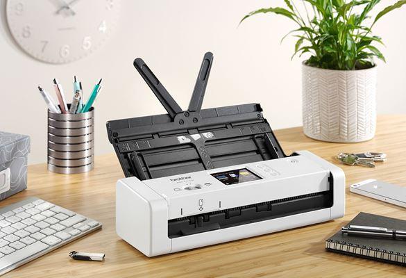 Brother ADS-1700W atidarytas kompaktiškas dokumentų skaitytuvas ant medinio stalo šalia augalo ir klaviatūros