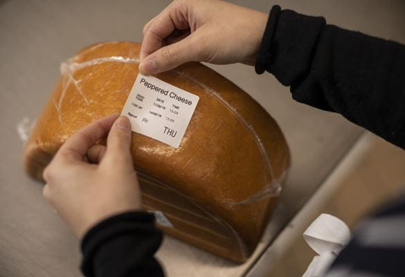 A member of a kitchen staff team applies a food information day label onto a block of peppered cheese