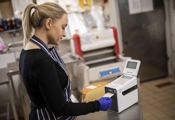 A female member of staff is printing a food label from a Brother labelling machine to add to a wheel of cheese in the back office of a food deli or cafe.