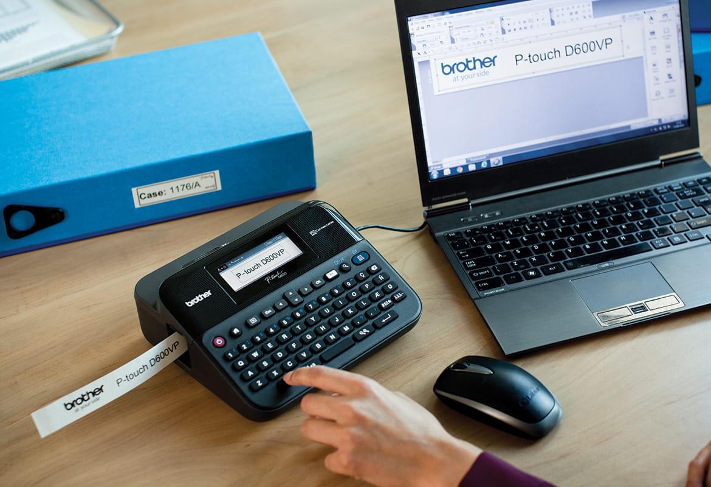 En person skriver ut merkelapper på en Brother P-touch merkemaskin som står på et skrivebord og er koblet til en bærbar datamaskin