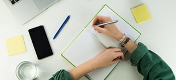 taking notes on a desk with mobile phone visible