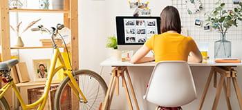 En kvinne med gul T-skjorte sitter på sitt hjemmekontor hvor hun har sin gule sykkel stående
