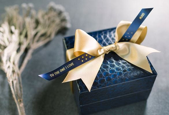 Gift box wrapped with a generic yellow ribbon, and Brother gold on blue satin ribbon with printed message