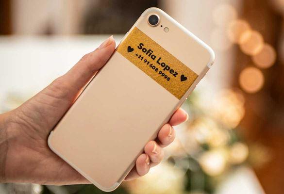 En smarttelefon er merket med en Brother merkelapp med sort tekst på premium glitrende gull som viser eierens navn og kontaktnummer