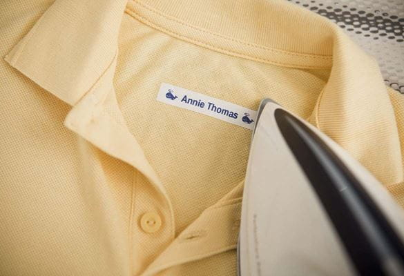 Child's polo shirt being labelled with an iron-on label showing the child's name.