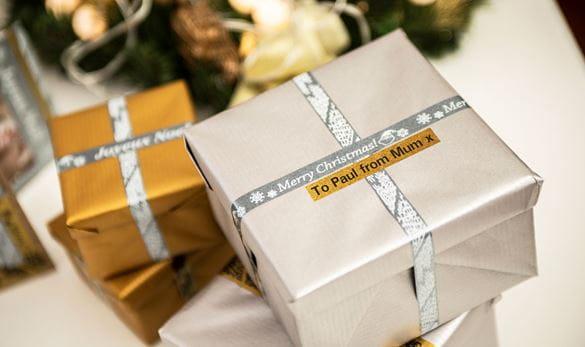 To julegaver pakket inn med papir i sølv og gull pyntet med merkelapper i glitrende sølv og gull med en personlig melding printet på en Brother P-touch CUBE merkemaskin