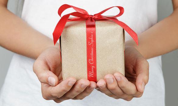 En person holder en Julegave i hendene, pent innpakket i et rødt silkebånd med en personlig melding trykt på båndet