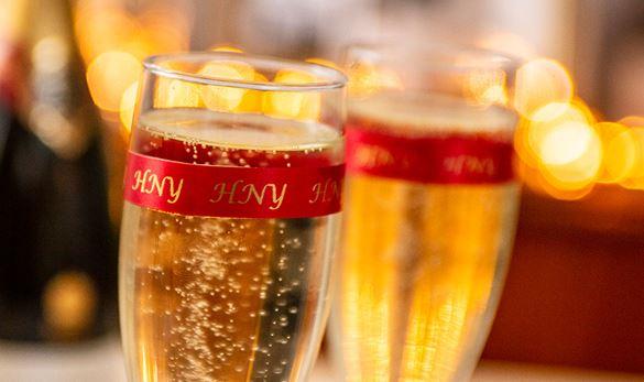 To champagneglass pyntet med et rødt Brother silkebånd med teksten HNY (godt nytt år)