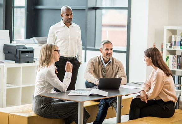 Cilvēku grupa birojā pie galda ar Brother mono lāzerdrukas printeri
