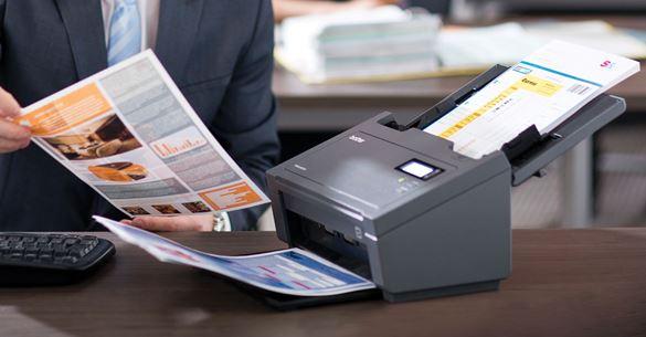 En mann skanner flere dokumenter i farger