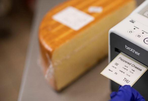 Närbild på en Brother-etikettskrivare som skriver ut en datumetikett till en ostbit på en matdeli eller café