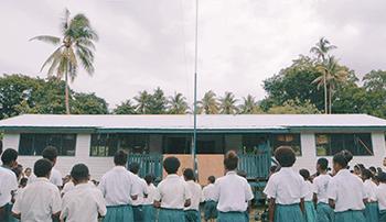 Skoleelever i hvite skjorter står utenfor en skole