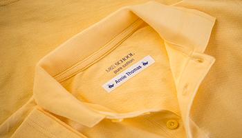 Gul poloskjorte med navnelapp som er festet inni skjorten