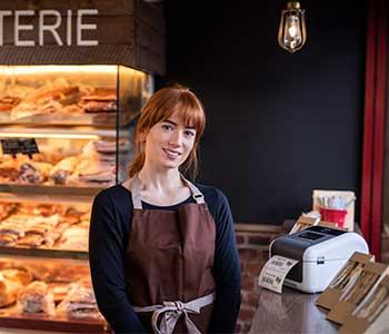 Kvinne med et brunt forkle i en kafe med en smørbrød og en TD-etiekttskriver ved siden av seg.
