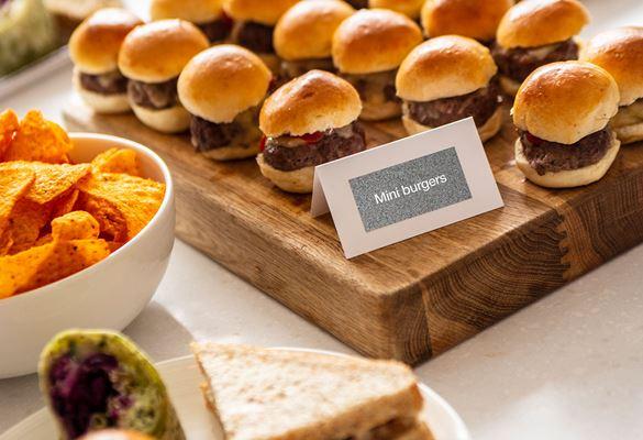 Brett med mini hamburgere, tallerken med sandwich, hvitt matkort med sølvfarget tape med hvit skrift