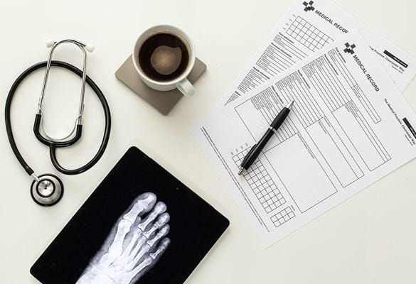 Medical forms, pen, cup of coffee on coaster, stethoscope, tablet with xray of foot on white table