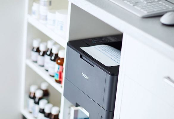 Brother HL-L2375DW mono laser printer in a pharmacy under counter next to medication