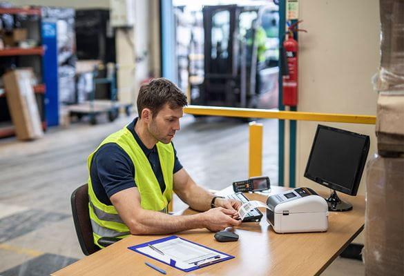 Varastomies istuu työpisteessään ja tulostaa lähetystietoja Brotherin etikettitulostimeen