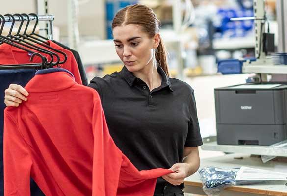 En kvinne på et varemottak holder i en rød jakke med kleshenger, en Brother laserskriver står i bakgrunnen