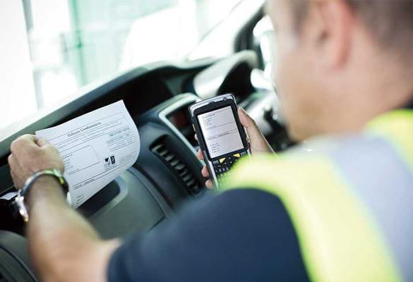 Mannlig sjåfør i gul vest skriver ut et dokument mens han er i bilen