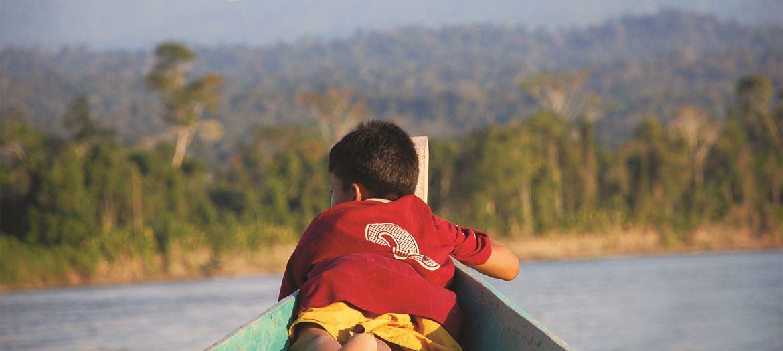 En gutt med rød t-skjorte ligger i en båt