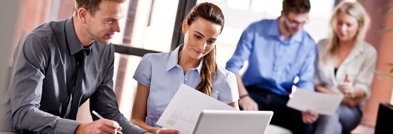 En gruppe mennesker studerer utskrevne dokumenter på et kontor