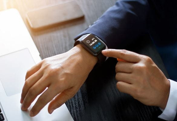 A man in a suit jacket is seen using wearable technology in the form of a smartwatch in the workplace of the future