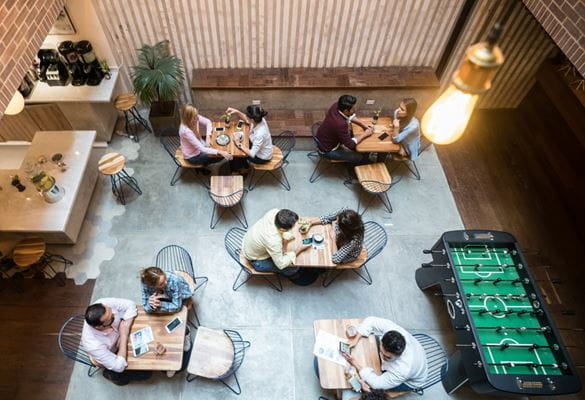Fremtidens arbeidspalass sees fra oven og vi ser et pent minimalistisk kontor med bord og et spillbord