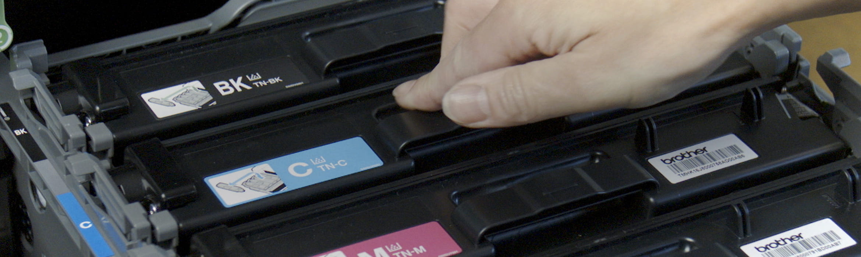 En person setter inn tonerkassetter i en skriver