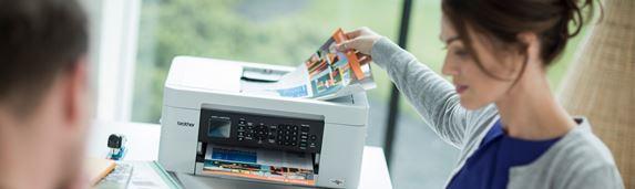 En kvinne legger et fargerikt dokument i arkmateren på en skriver
