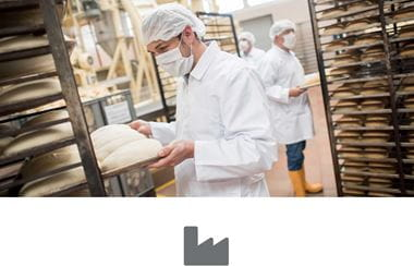 Men working at an industrial bakery and about to put bread in the oven