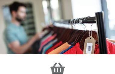 Et klesstativ med klær i en klesbutikk med en mann i bakgrunnen