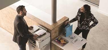 Ylhäältä otettu kuva naisesta ja miehestä juttelemassa Brother-tulostimen vieressä