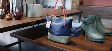 Håndveske, sko og klær utstilt på et bord i en butikk